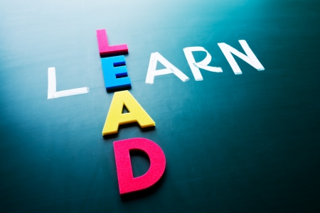 learn and lead: Lead and learn, conceptual words on blackboard Stock Photo