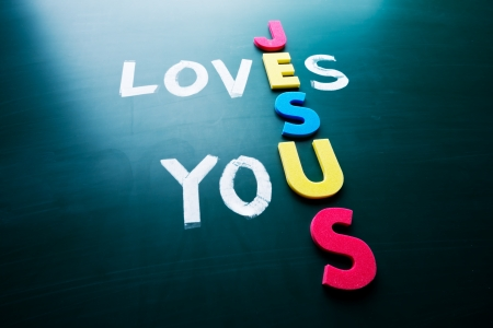 loves: Jesus loves you, conceptual words on blackboard