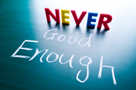 great success: Never good enough concept, words on blackboard