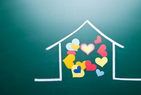 Family love concept, colorful heart shape in drawing house on blackboard photo