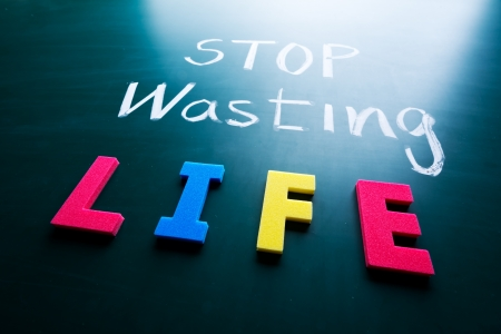 Stop wasting life concept, colorful words on blackboard photo