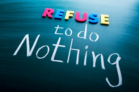 refuse: Refuse to do nothing, conceptual words on blackboard