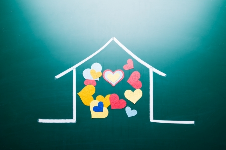 Family love concept, drawing house and colorful heart shape on blackboard photo