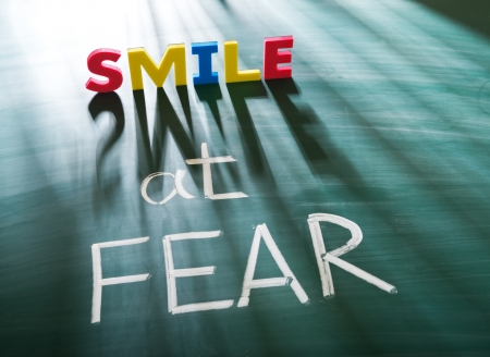 Smile at fear, conceptual words on blackboard Stock Photo - 19559662