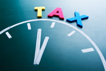 tax return: Time for tax concept, color word and clock on blackboard
