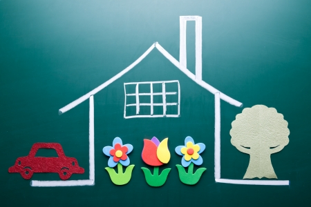 Drawing house on blackboard with handmade tree, car and flowers as decoration. photo
