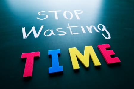 waste money: Stop wasting time concept, colorful words on blackboard Stock Photo