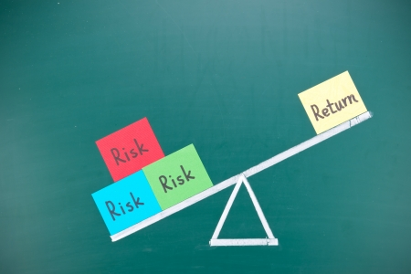 stock market return: Return and risk imbalance concept, words and drawing on blackboard  Stock Photo