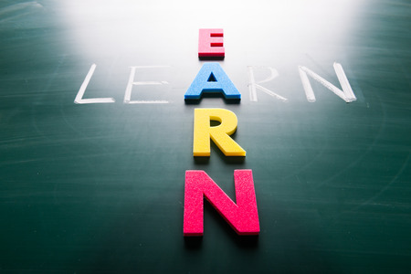financial adviser: Learn and earn, words on blackboard with colorful alphabets.