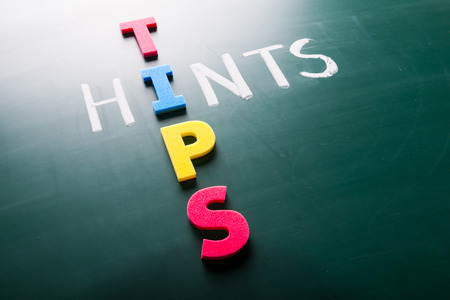 hints: Hints and tips, words on blackboard with colorful alphabets. Stock Photo