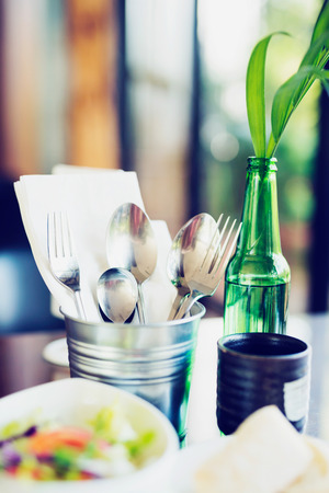 dinning table: Tablewares in steel can on dinning table