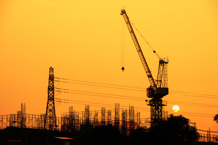 pylon: Industrial building site and electric pylon at sunset silhouetted against a colorful orange sky with a crane in the foreground