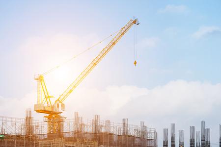 Baustelle mit Hochhaus im Bau in einem städtischen Umfeld mit einer großen Industriekran gegen einen bewölkten blauen Himmel ab dominiert