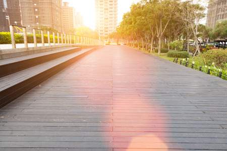 recreational area: Deserted walkway and bench steps in an urban park surrounded by high-rise commercial buildings , low angle view Stock Photo