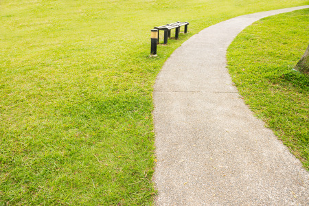 manicured: Single Wooden Bench at the Park, with Fresh Green Grasses, Along Narrow Human Pathway. Stock Photo