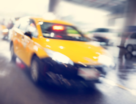 terminus: Bright yellow iconic taxi cab speeding past the illuminated entrance of an airport terminus building with motion blur of the car Stock Photo