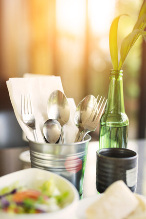 Tablewares in steel can on dinning table photo