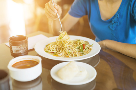 Female eating meal set of spaghetti, bread and soup photo