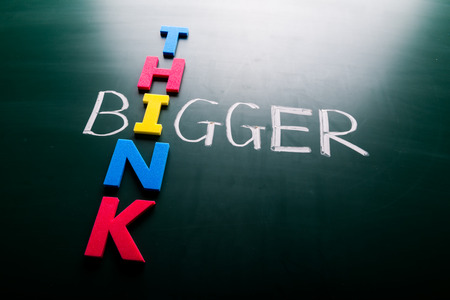 Simple Think Bigger Concept, with Colorful THINK Letters Crossing on BIGGER Text at Green Chalkboard photo