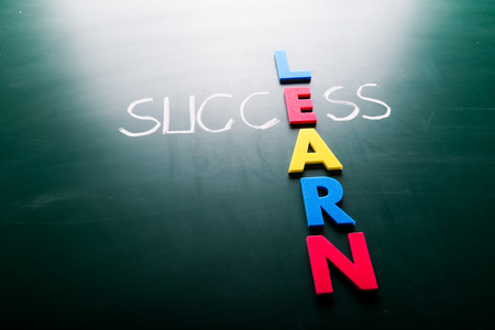 Simple Learn and Success Concept Formed in Cross with Dark Chalkboard Background. photo