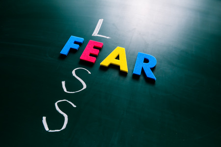 dauntless: Colorful word fear and writing word less crossing on blackboard Stock Photo