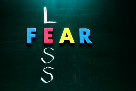 plucky: Colorful word fear and writing word less crossing on blackboard Stock Photo