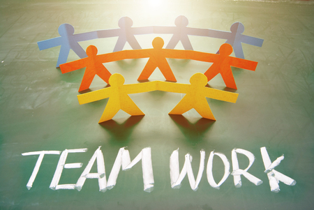 depend: Teamwork words and colorful paper dolls on  blackboard