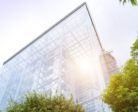 low angle views: Low angle view past green foliage of the transparent glass facade of a contemporary urban skyscraper in an architectural background Stock Photo