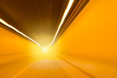 undercover: Bright orange light at the end of an undercover traffic tunnel or underpass with receding interior perspective