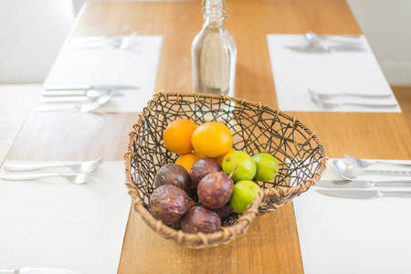 napkin: Fruits in heart shape basket on dining table with dishwares on white napkin