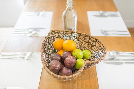 �napkin: Frutas en la cesta de forma de coraz�n en la mesa de comedor con dishwares en la servilleta blanca Foto de archivo