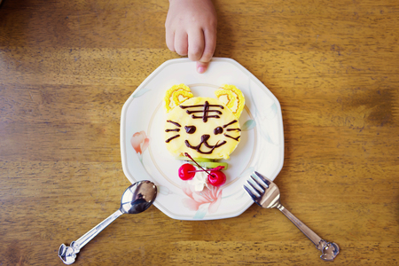 decorated cake: A cute tiger decorated cake with a kids hand background.
