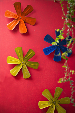 floral objects: Colorful metal flowers decoration on red wall.
