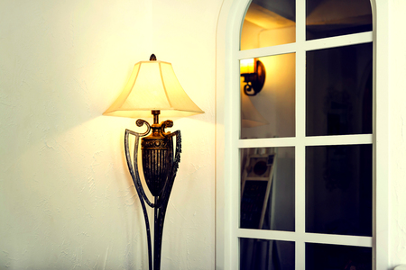 floor lamp: Antique brass floor lamp beside white wall and grille window Stock Photo