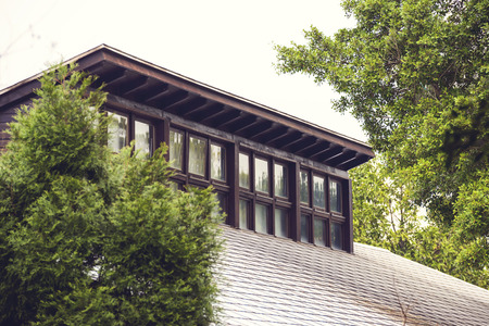 windowpanes: Dormer windows on a building rooftop with a tiled roof surrounded by green leafy trees reflected in the glass