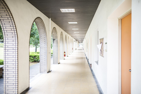 openair: School long straight open-air passage lined with tiled white arches leading to a garden with doors with receding perspective