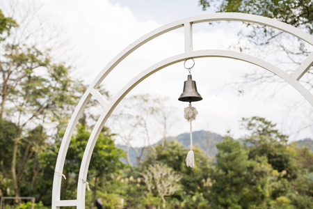 curfew: Small bell with rope hanging on white iron arch
