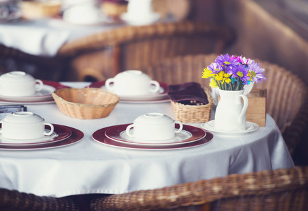 hospitality: Table set for dinner in a restaurant or bistro with dinnerware and linen and a small vase of colorful flowers