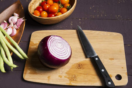 garlics: Fresh ingredients- onion, cherry tomatos, garlics and beans for cooking on wooden board.