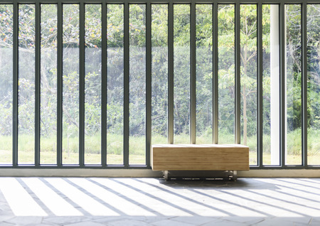 window bench: Wooden bench in front of French window with sunlight and countryside view