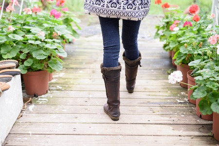 Womans legs in boots walking along wooden path