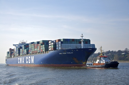 a container ship being towed by a tugboat in the harbor Editorial