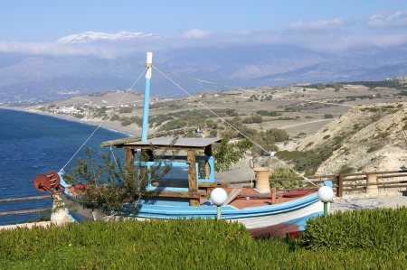 ida: A small fishing boat on land in the south of Crete in the background the Komos beach and the snowy mountains Ida