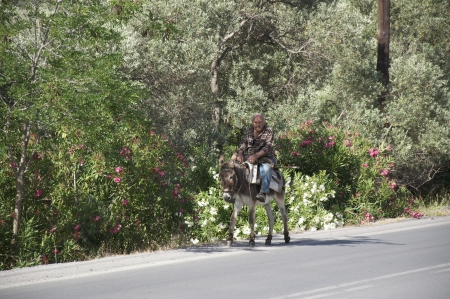 Old man riding a donkey on the street on Crete  In the mountains on Crete the donkey is still used as a means of transportation
