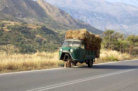 kaput: Defective old three wheel truck with hay load on the road on Crete  The Truck is on the road to Rethimno, close to the Ida mountains with the Psiloritis as the highest elevation Stock Photo