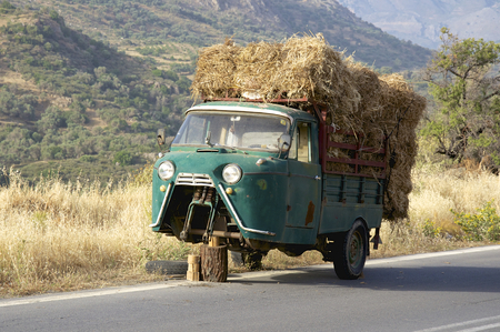 Defective old three wheel truck with hay load on the road on Crete  The Truck is on the road to Rethimno, close to the Ida mountains with the Psiloritis as the highest elevation Stock Photo