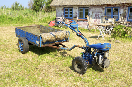 Two-wheel Tractor in front of a Thatched House on the Warft on the Hallig Langeness