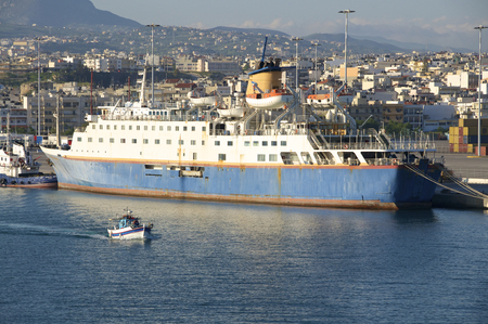 Old Cruise Ship in the harbor of Heraklion on Crete. In the foreground, a fishing boat leaves the harbor. With approx. 180,000 inhabitants, is the capital Heraklion from Crete