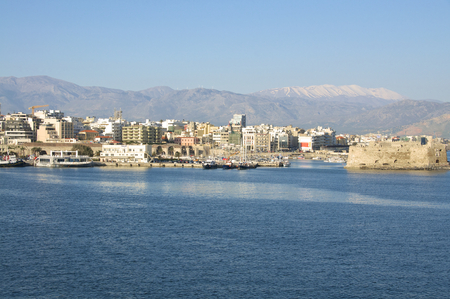 ida: View to the fishing port in the Venetian harbor of Heraklion on April 10, 2014. Iraklio is the capital on Crete. In the background, the snowy IDA Mountains
