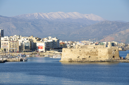 ida: View to the fishing port in the Venetian harbor of Heraklion. Heraklion is the capital on Crete. In the background, the snowy IDA Mountains Editorial